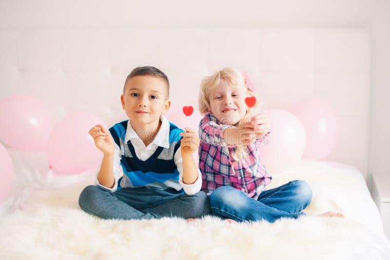 duas crianças engraçadas adoráveis bonitos caucasianos brancas felizes que comem pirulitos dados forma coração foto de stock royalty free