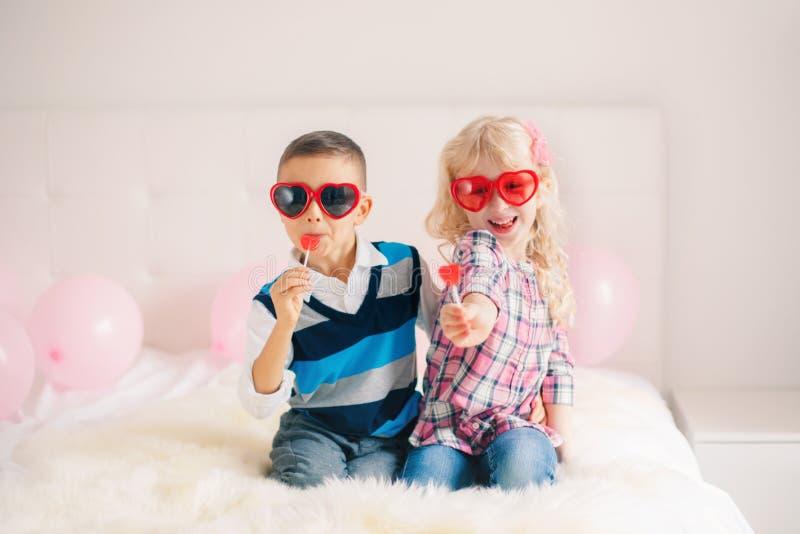 duas crianças engraçadas adoráveis bonitos caucasianos brancas felizes que comem pirulitos dados forma coração imagem de stock royalty free