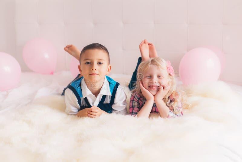 duas crianças engraçadas adoráveis bonitos caucasianos brancas felizes que encontram-se na cama foto de stock royalty free