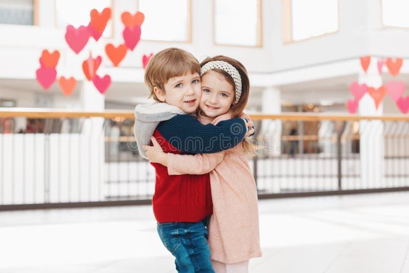 Duas crianças engraçadas adoráveis bonitos caucasianos brancas menino e menina que abraçam o beijo fotografia de stock