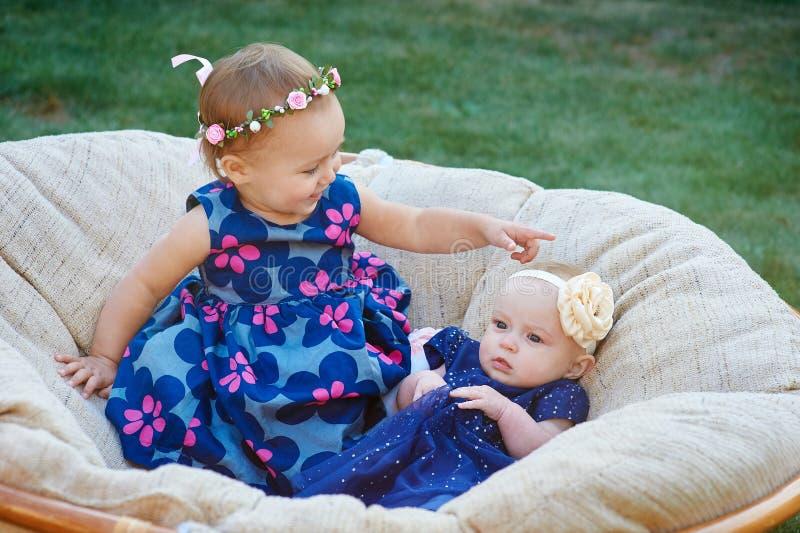 Duas crianças engraçadas que sentam-se na luz suave presidem junto no parque da mola imagens de stock royalty free