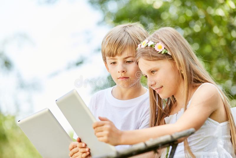 Duas crianças estão olhando curiosamente a tabuleta fotografia de stock royalty free