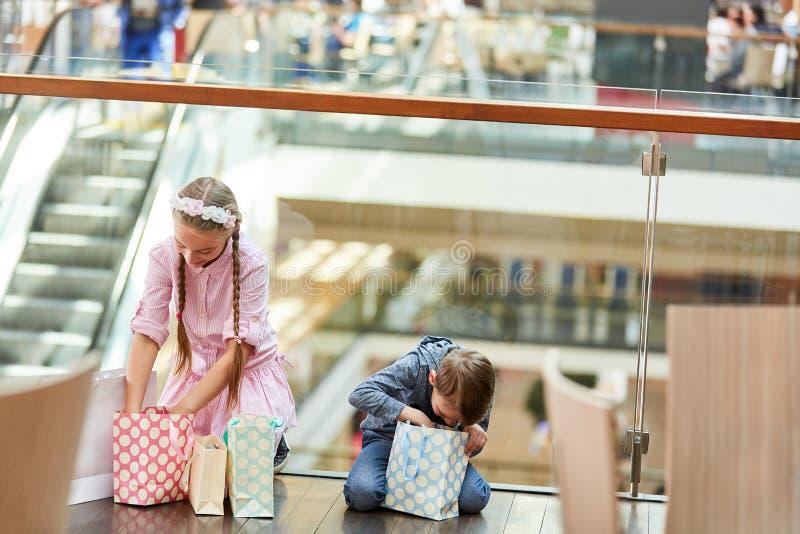 Duas crianças estão olhando em seus sacos de compras fotos de stock royalty free