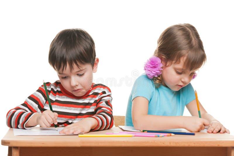 Duas crianças escrevem na mesa fotografia de stock royalty free