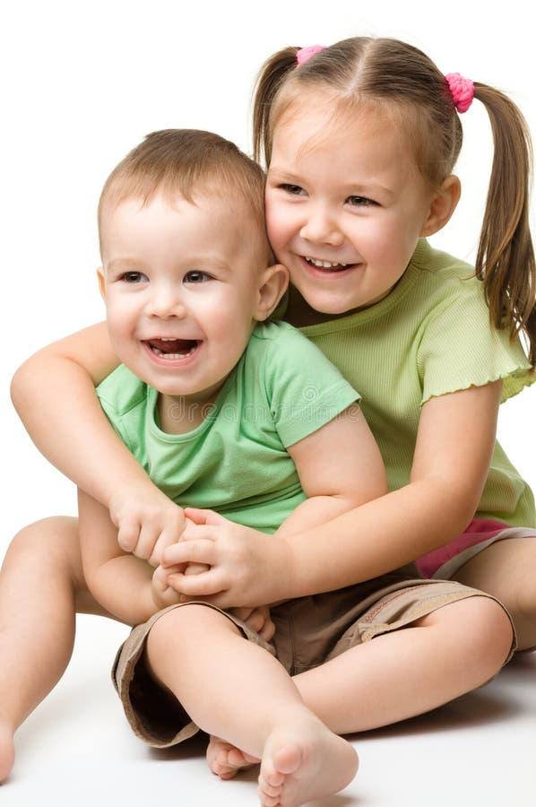 Duas crianças estão tendo o divertimento ao sentar-se no assoalho imagens de stock royalty free