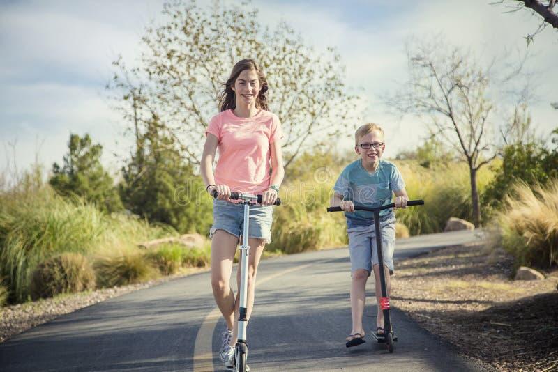 Duas crianças felizes em um 'trotinette' montam fora em um caminho pavimentado foto de stock