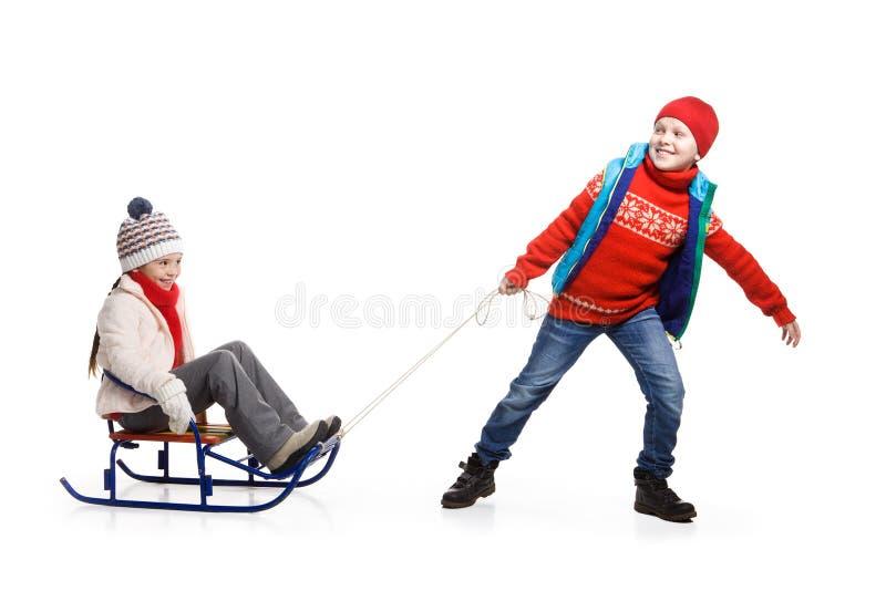 Duas crianças felizes na roupa do inverno no trenó foto de stock