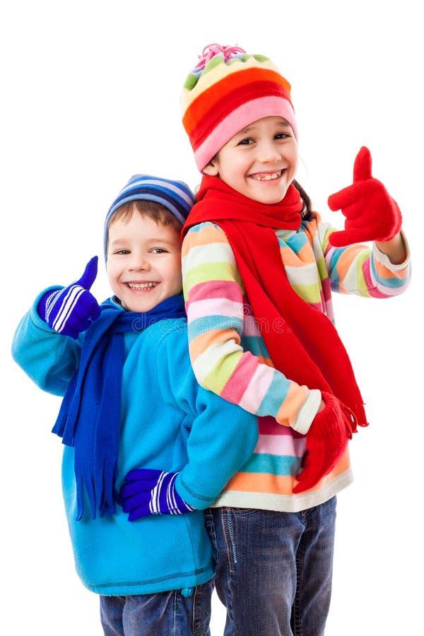 Duas crianças felizes no inverno vestem-se com os polegares acima do sinal imagem de stock royalty free
