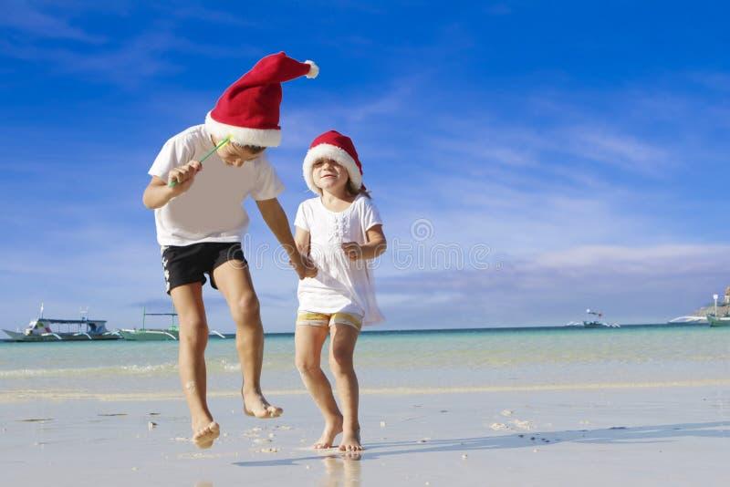 Duas crianças felizes novas em chapéus de Santa na praia tropical fotos de stock