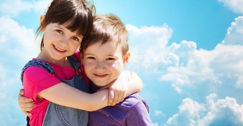 Duas crianças felizes que abraçam sobre o céu azul e as nuvens foto de stock