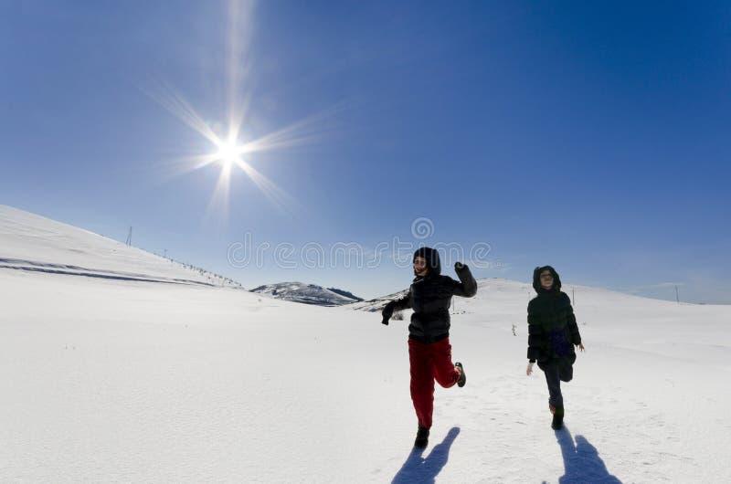 Duas crianças felizes que correm na neve em uma montanha e em um sol que brilham imagem de stock royalty free