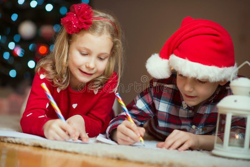 Duas crianças felizes que escrevem a letra a Santa Claus em casa perto do Ne imagem de stock
