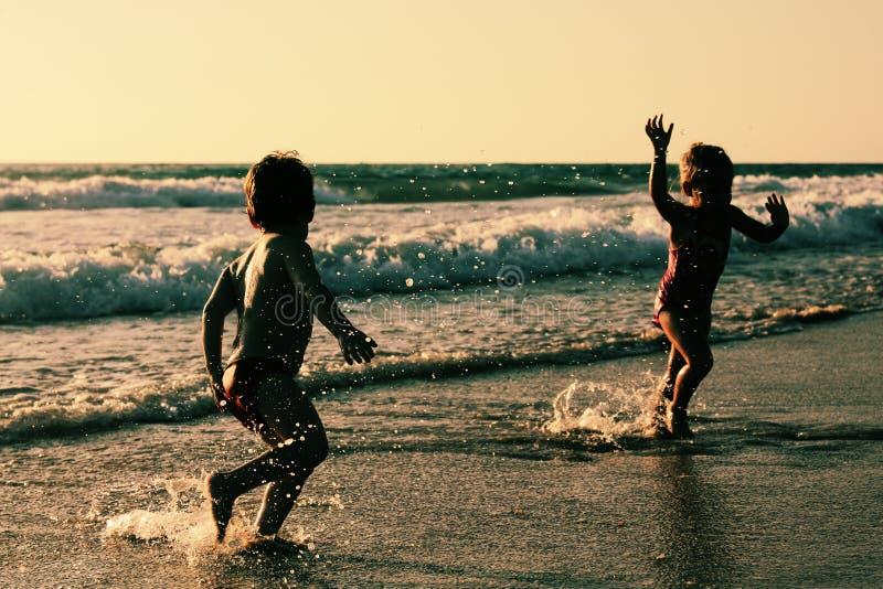 Duas crianças felizes que jogam na praia foto de stock