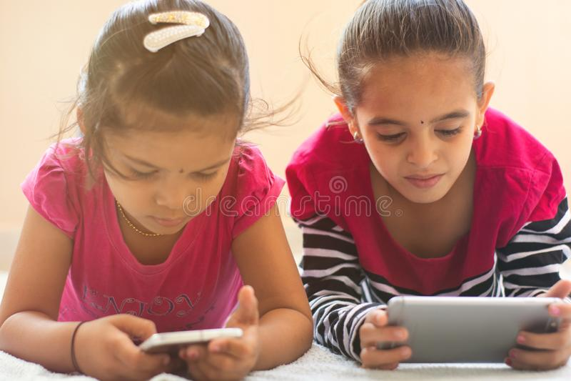 Duas crian?as indianas bonitos ocupadas no telefone celular de observa??o na cama imagem de stock royalty free