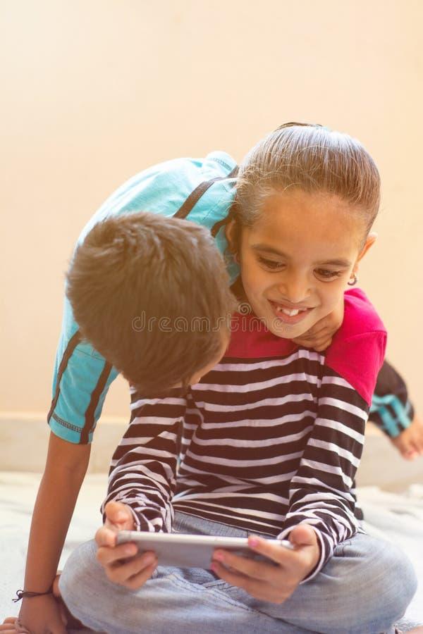 Duas crianças indianas pequenas bonitos que têm o divertimento olhando o dispositivo móvel em casa fotos de stock royalty free