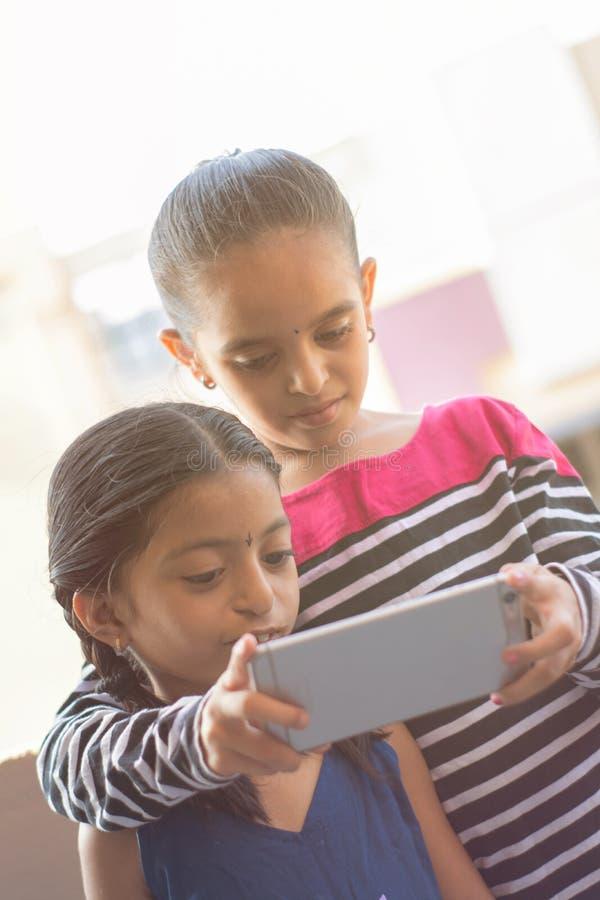 Duas crianças indianas que olham o dispositivo móvel em exterior foto de stock royalty free
