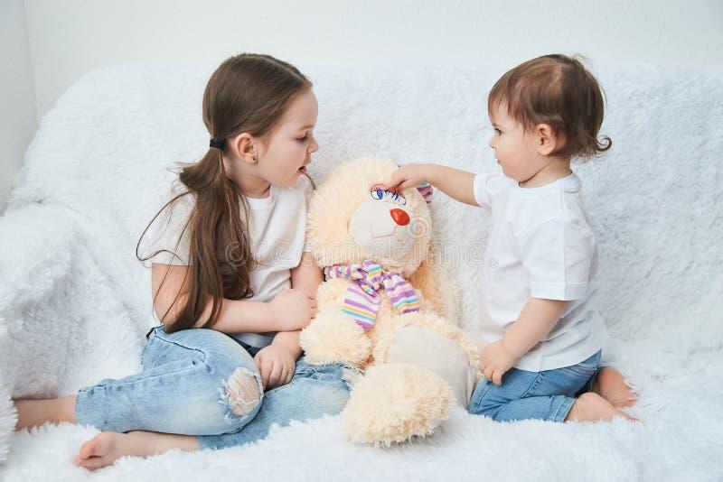 Duas crianças, irmãs jogam em um sofá branco nos t-shirt e na calças de ganga brancos Coelho macio do luxuoso fotos de stock