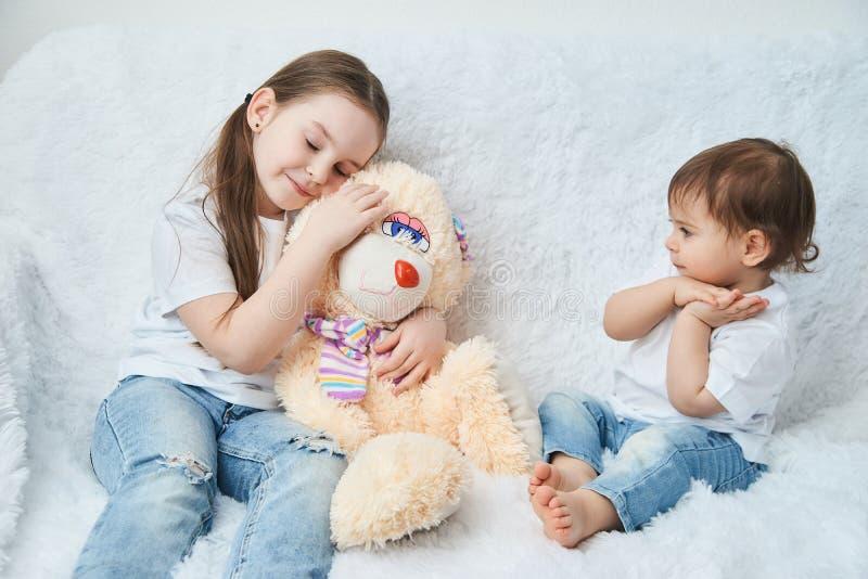 Duas crianças, irmãs jogam em um sofá branco nos t-shirt e na calças de ganga brancos Coelho macio do luxuoso imagem de stock