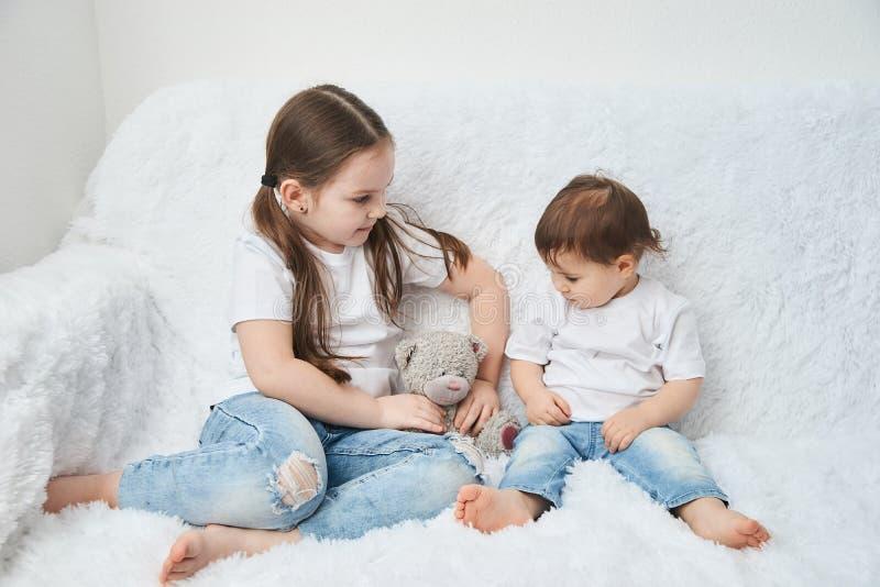 Duas crianças, irmãs sentam-se em um sofá branco nos t-shirt e na calças de ganga brancos Urso macio do luxuoso imagem de stock royalty free