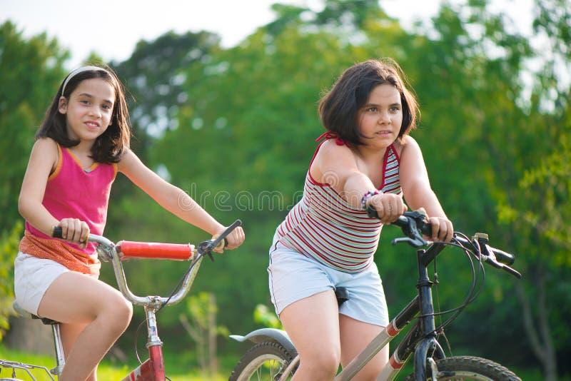 Duas crianças latino-americanos que montam em bicicletas imagens de stock