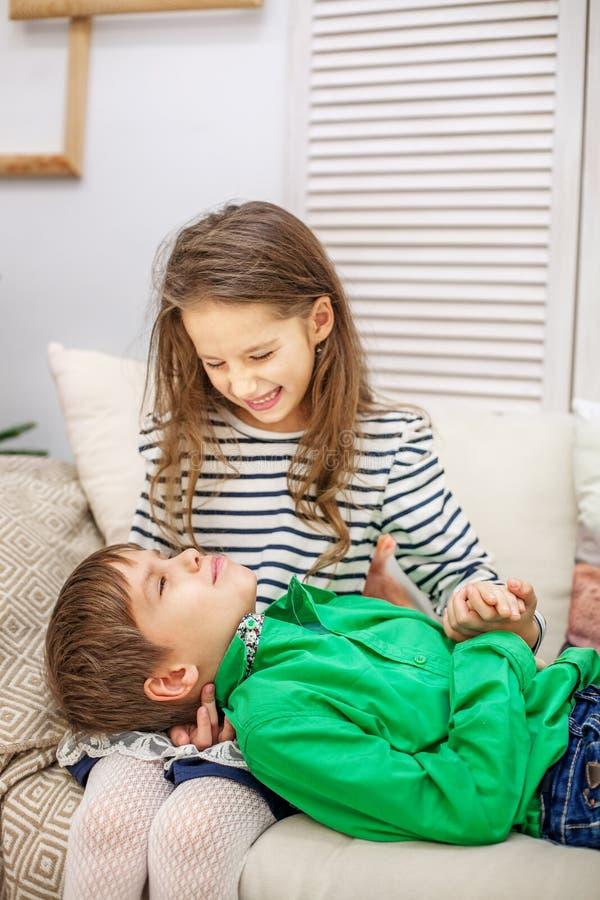 Duas crianças lounging no sofá O menino e a menina Th foto de stock