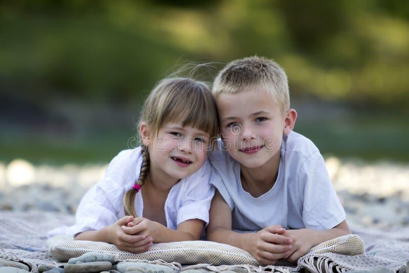 Duas crianças louras bonitos felizes novas, menino e menina, irmão e irmã colocando na praia pebbled no dia de verão ensolarado b foto de stock royalty free