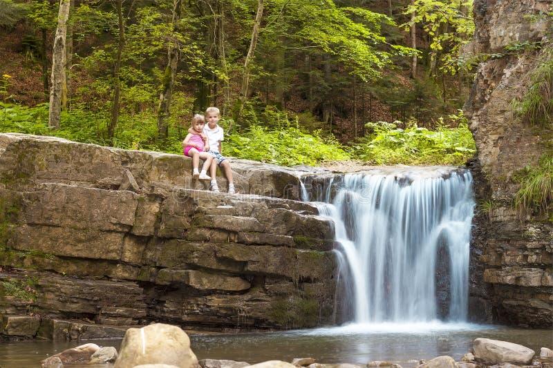 Duas crianças menino e menina que sentam-se perto da cachoeira na floresta fotos de stock