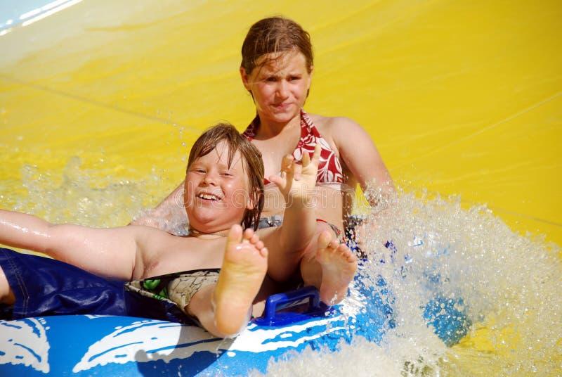Duas crianças na corrediça de água imagens de stock royalty free