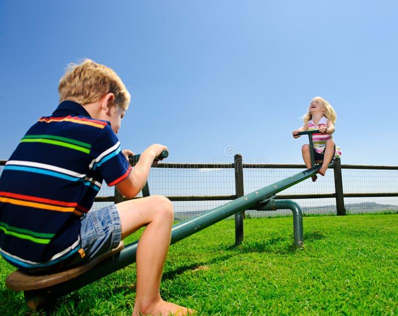 Duas crianças no campo de jogos fotos de stock royalty free