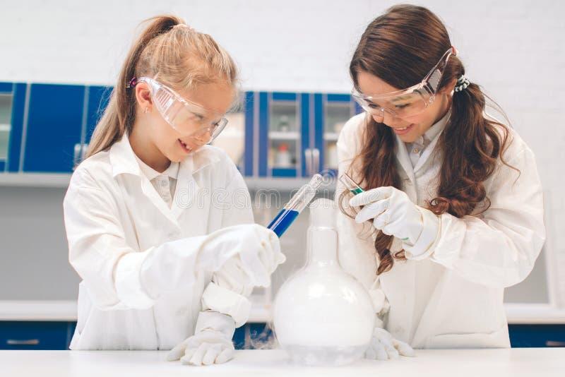 Duas crianças no laboratório revestem a aprendizagem da química no laboratório da escola Cientistas novos na fatura protetora dos foto de stock royalty free