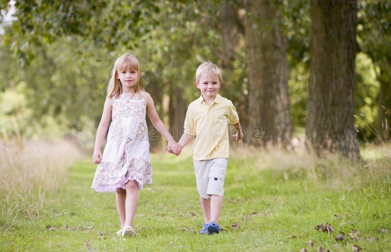 Duas crianças novas que andam nas mãos da terra arrendada do trajeto imagem de stock