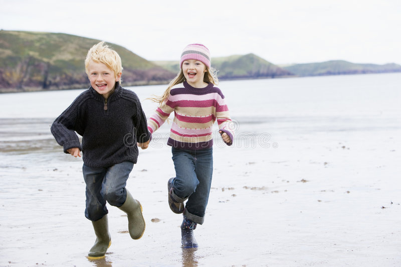 Duas crianças novas que funcionam nas mãos da terra arrendada da praia imagens de stock royalty free
