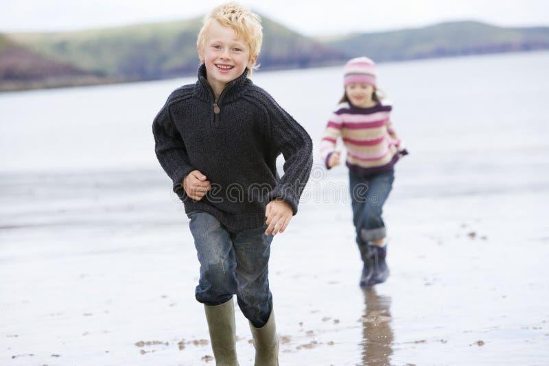 Duas crianças novas que funcionam no sorriso da praia fotos de stock