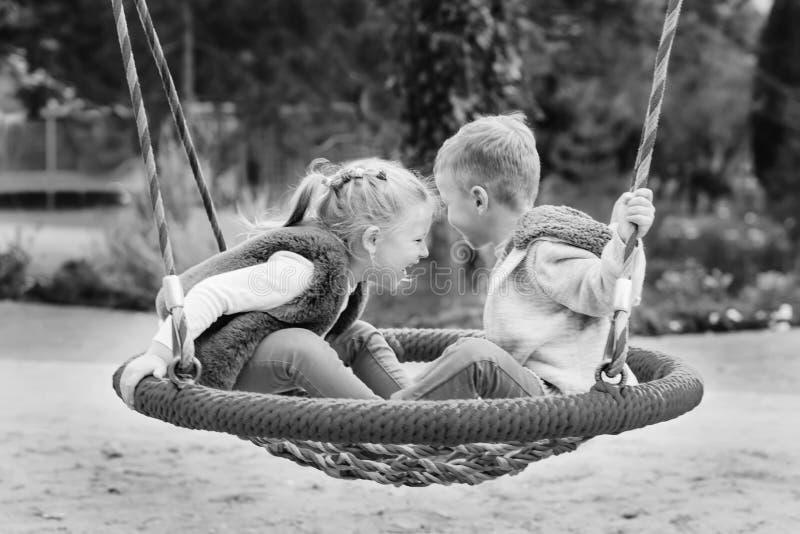 Duas crianças pequenas felizes que têm o divertimento em um balanço fotografia de stock royalty free
