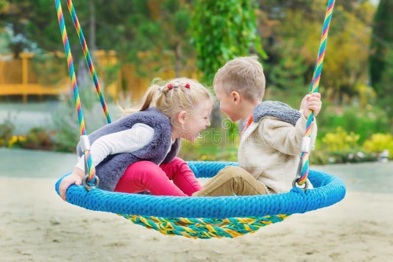 Duas crianças pequenas felizes que têm o divertimento em um balanço fotos de stock