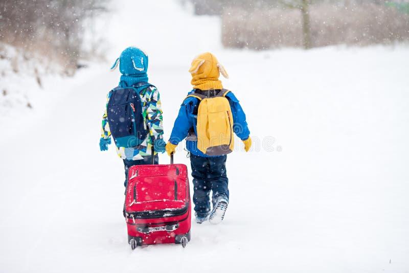 Duas crianças pequenas, irmãos do menino com trouxas e um vermelho grande s foto de stock