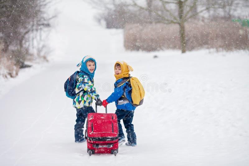 Duas crianças pequenas, irmãos do menino com trouxas e um vermelho grande s foto de stock royalty free