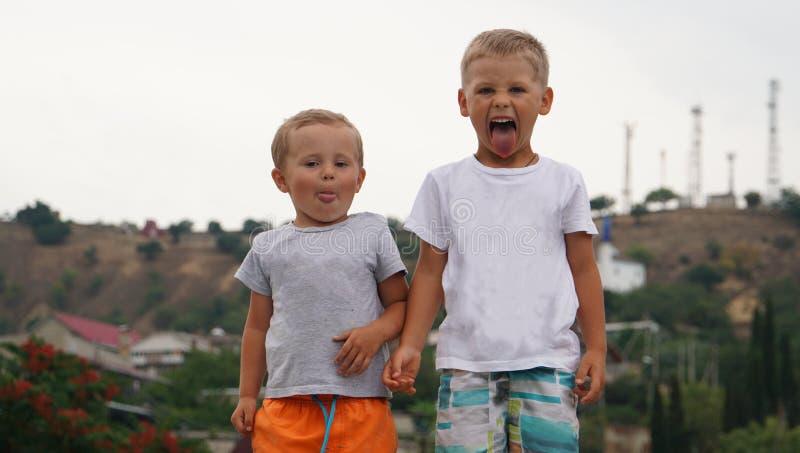 Duas crianças pequenas que jogam junto fora estar na costa do mar fotografia de stock