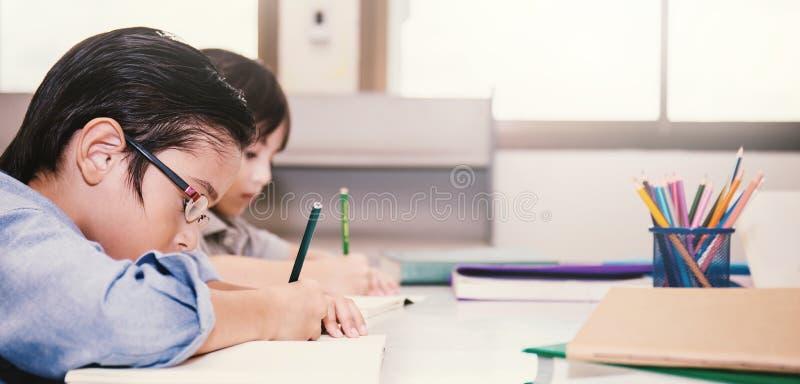 Duas crianças pequenas que sentam a mão que guarda o lápis e que colore a imagem foto de stock royalty free