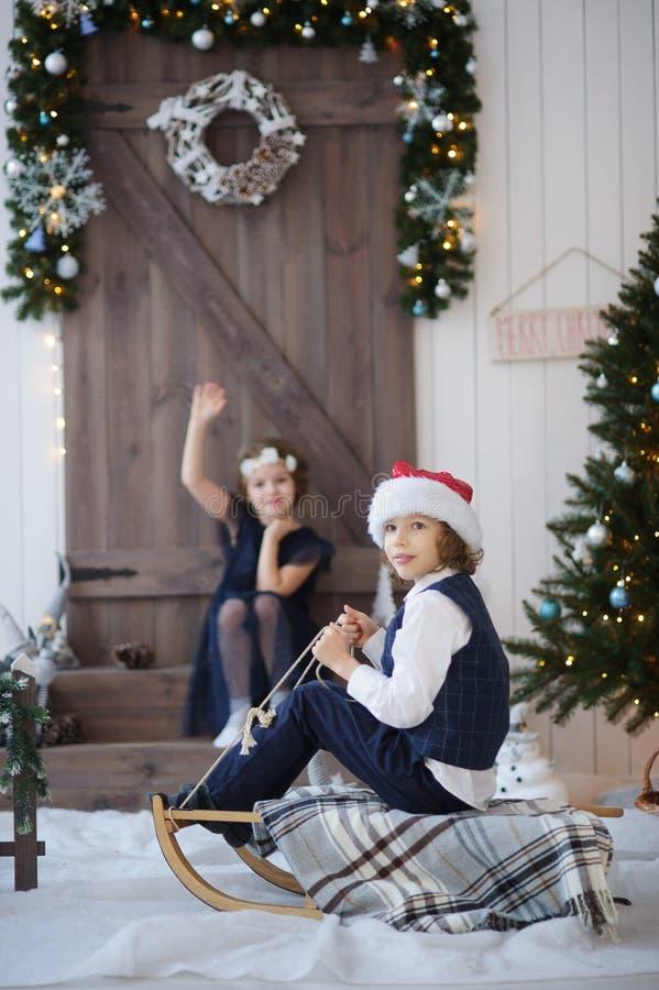 Duas crianças perto da porta de madeira decorada com festões e uma grinalda imagens de stock