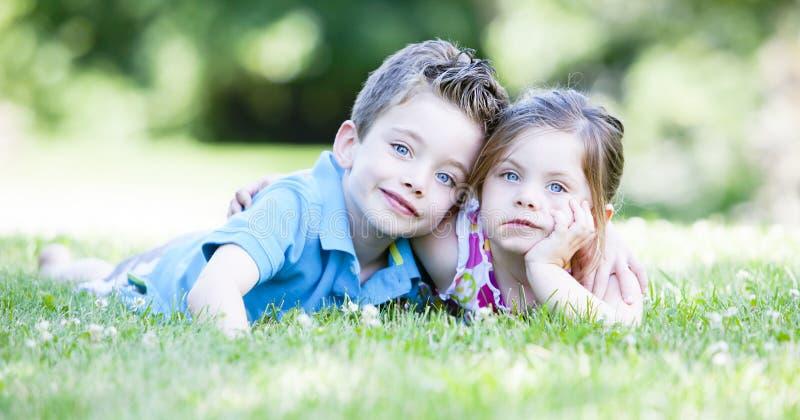 Duas crianças que colocam na grama foto de stock