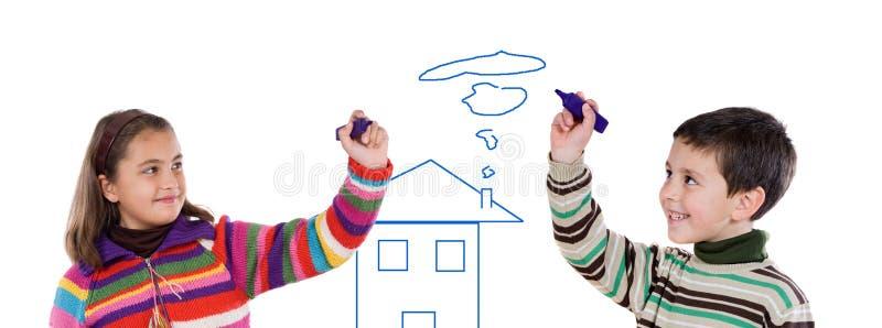Duas crianças que desenham uma casa fotografia de stock royalty free