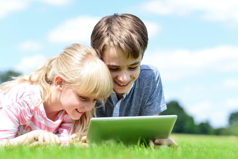 Duas crianças que encontram-se para baixo e que usam o PC da tabuleta fotos de stock