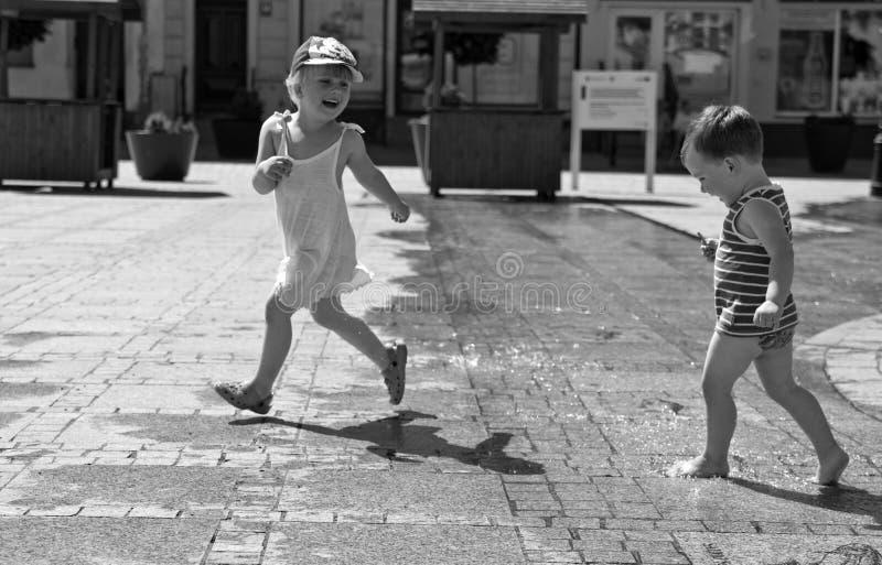 Duas crianças que jogam com água no quadrado de cidade pavimentado foto de stock