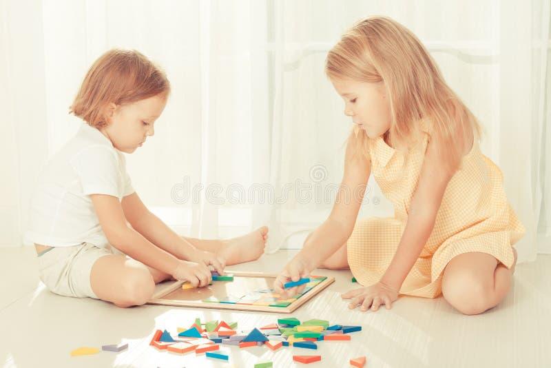 Duas crianças que jogam com o mosaico de madeira em sua sala imagem de stock