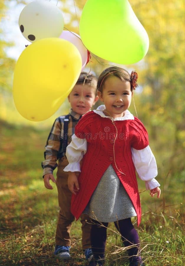 Duas crianças que jogam com os balões no parque imagens de stock royalty free