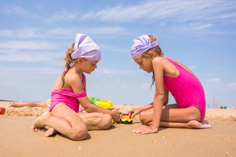 Duas crianças que jogam com os brinquedos na areia na praia do mar fotos de stock royalty free