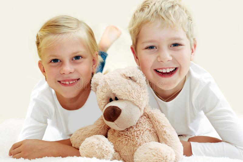 Duas crianças que jogam com um urso de peluche imagem de stock