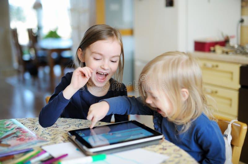 Duas crianças que jogam com uma tabuleta digital em casa imagens de stock royalty free