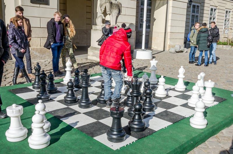 Duas crianças que jogam em partes de xadrez moventes enormes na placa no mercado central em Lviv, povos olham em torno delas em t imagens de stock